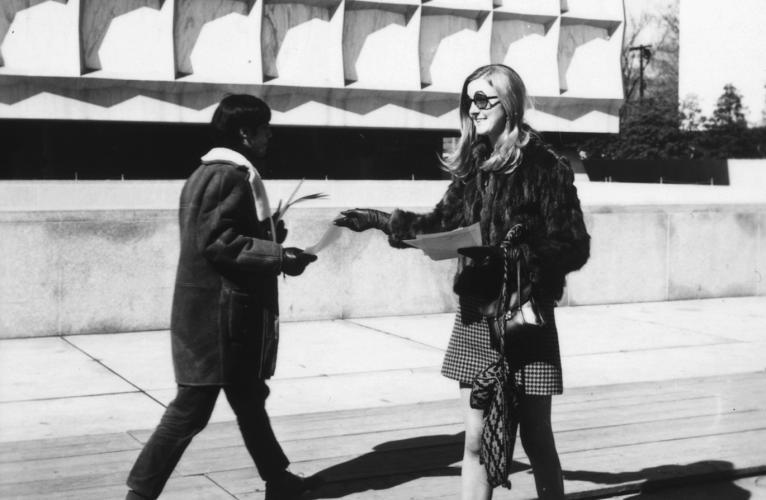 A female student in the early 1970's hands out a flyer to a passerby on campus with Beinecke Library in the background